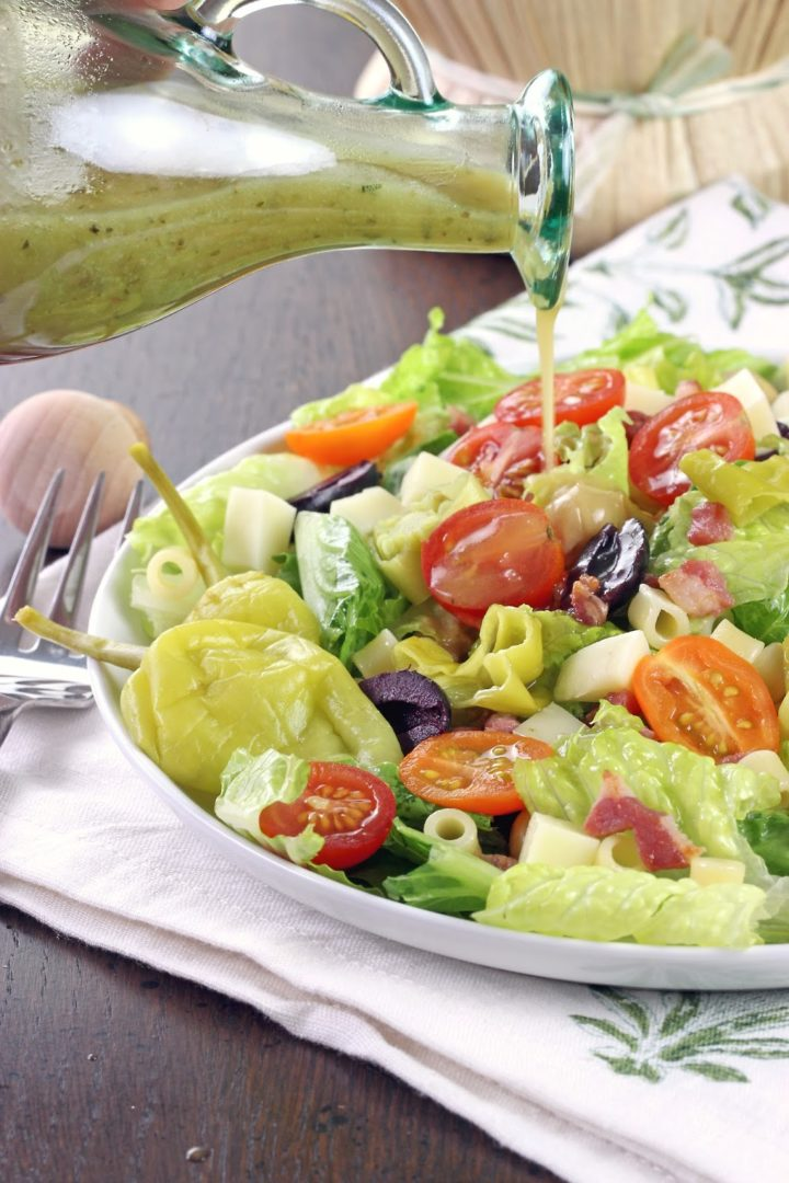 a bowl with lettuce, tomatoes, olives