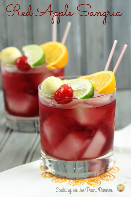 two red apple sangrias in short old fashioned glasses topped with orange, lime, cherry