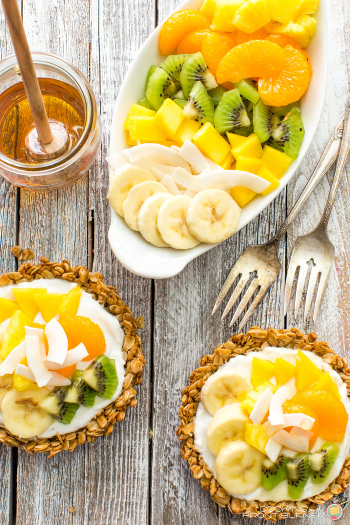 Breakfast granola tarts with creamy vanilla yogurt, topped with tropical fruits and drizzled with golden honey.