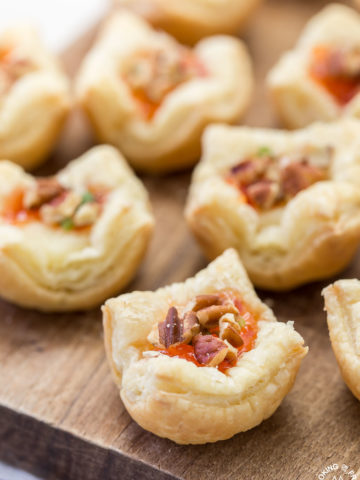 These Brie Pepper Jelly Bites are a great recipe to have on hand for the holidays!  You will love the flaky crust with brie and pepper jelly nestled inside.  Top with crunchy pecans and some green onions for a flavor explosion!