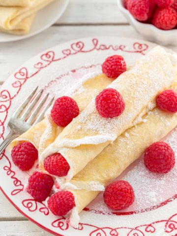 These Raspberry Vanilla Cream Crepes make the perfect dessert for Valentine's Day or any time you want to impress that someone special.  The crepes have a creamy vanilla filling and the fresh raspberries add a pop of color.