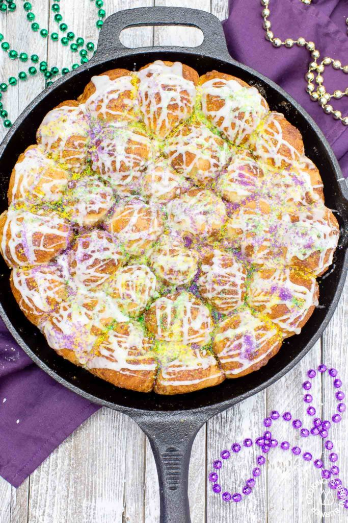 Your taste buds will be tantalized with these Skillet Cinnamon Rolls.  They are easy to make by starting with frozen rolls, the right amount of cinnamon and sugar and drizzled with a vanilla glaze.  Your kitchen will smell amazing too while they are baking! #breakfast #skilletrolls #cinnamon rolls #mardigras