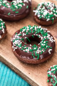 These chocolate Irish Cream Glazed Donuts are baked - not fried - and have a thick layer of chocolate ganache and festive sprinkles. They are so easy to make and are perfect for breakfast for a sweet treat! #donuts #chocolate #ganache #irishcream #baked