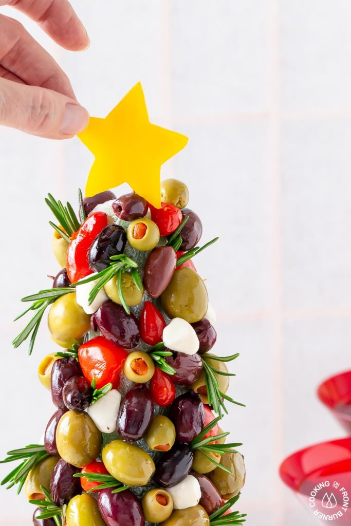 adding a yellow pepper star to an olive tree appetizer