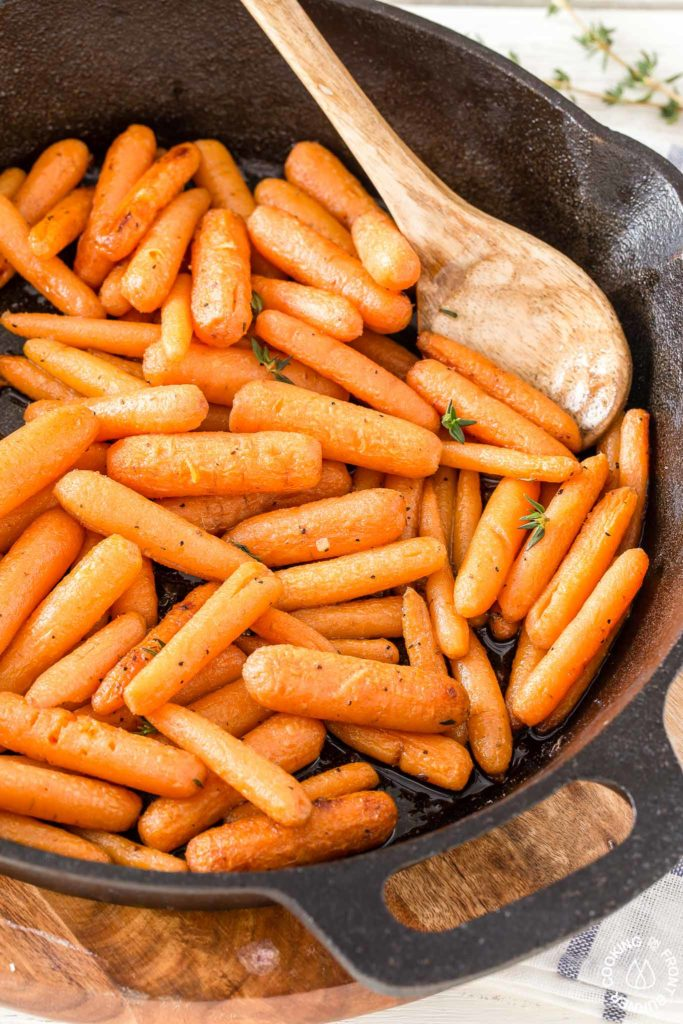 glazed carrots in a skillet with a serving spoon