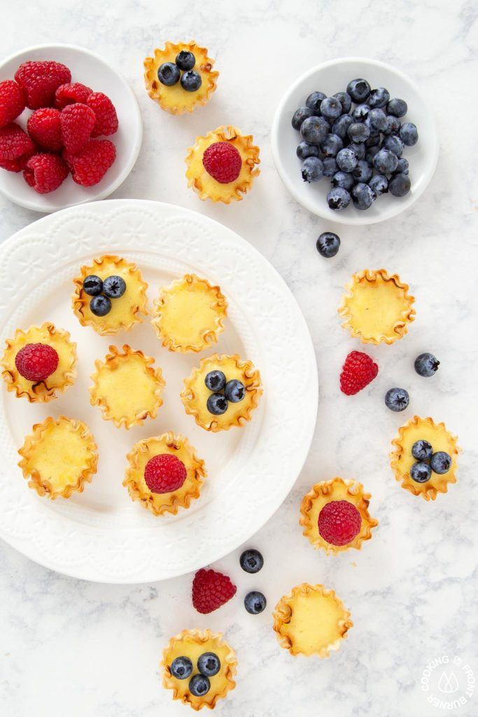 tarts on a plate with bowls of raspberries and blueberries