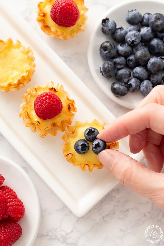 placing a blueberry on a lemon tart