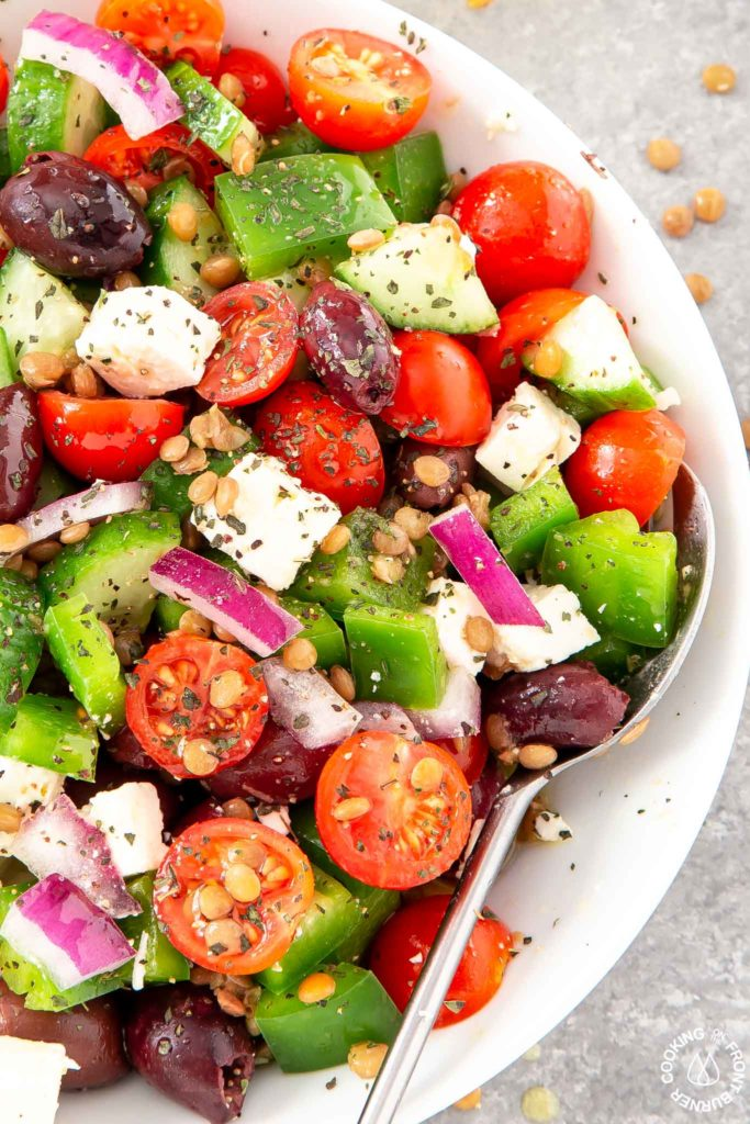 a bowl with greek salad mixed up with a spoon