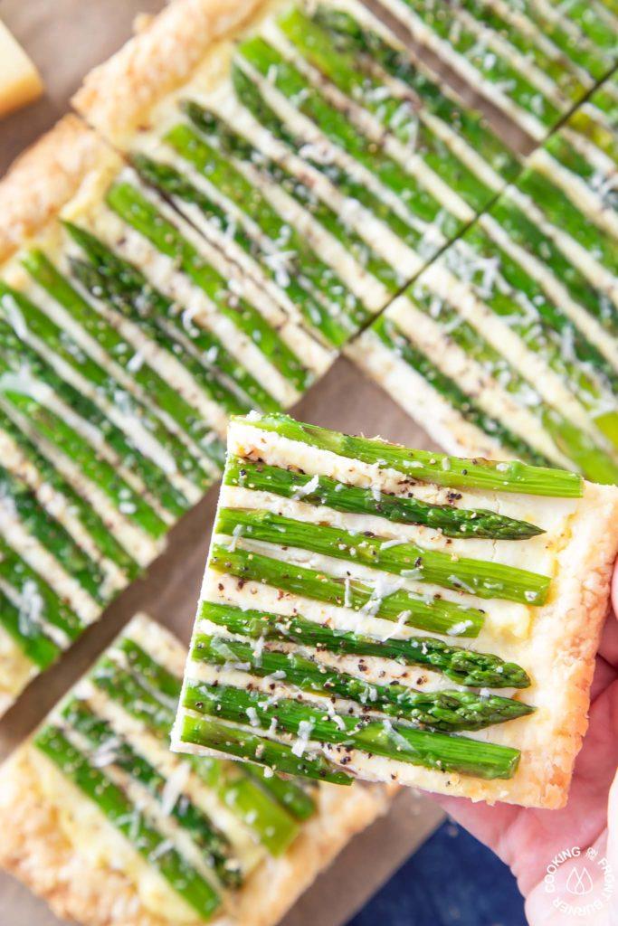 a slice of asparagus tart on a hand