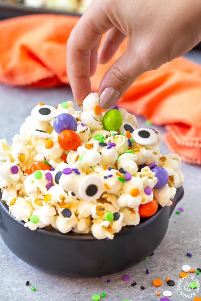 a hand taking a piece out of bowl of halloween snack mix