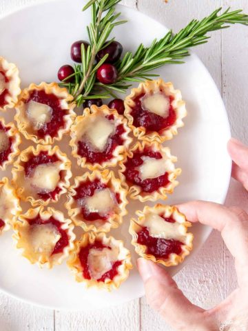 cranberry orange brie tarts on a plate with a hand taking one off