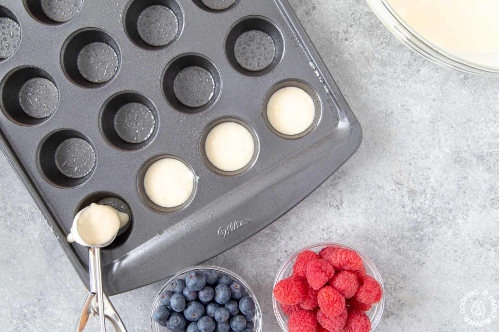 scooping pancake batter into mini muffin pan