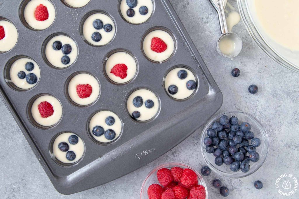 mini muffin pan with batter and topped with blueberries and raspberries