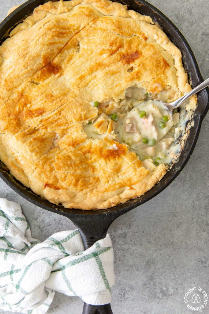 chicken pot pie in a skillet with a serving spoon