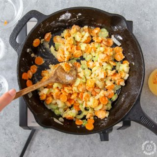 stirring veggies with flour in a skillet for chicken pot pie