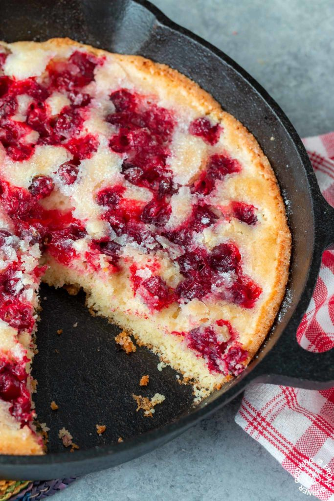 cranberry skillet bread with a slice out of the skillet