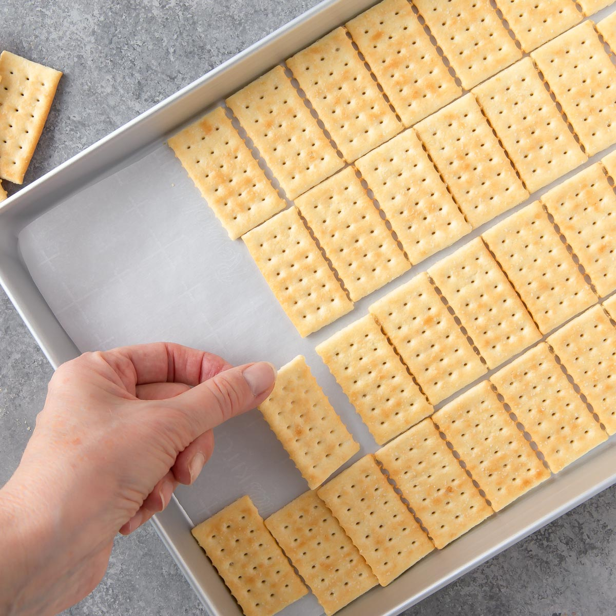 jelly roll pan with a hand placing crackers on it