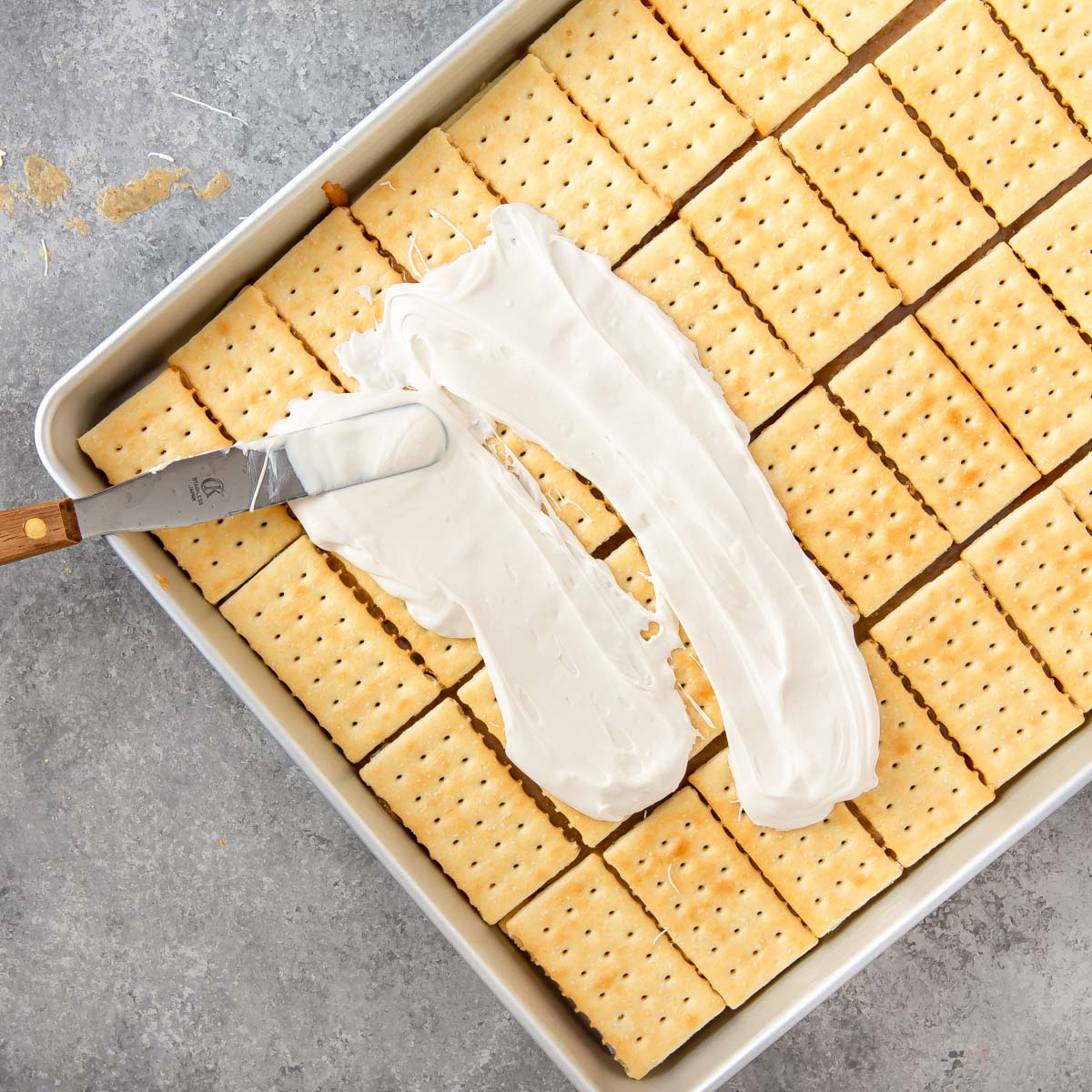 spreading melted white chocolate on toffee bars