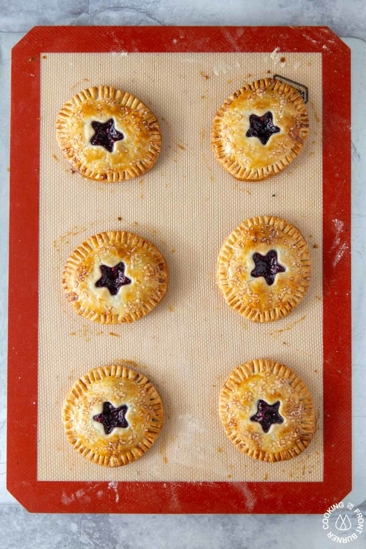 6 blackberry hand pies on a cookie sheet out of the oven - they are golden brown