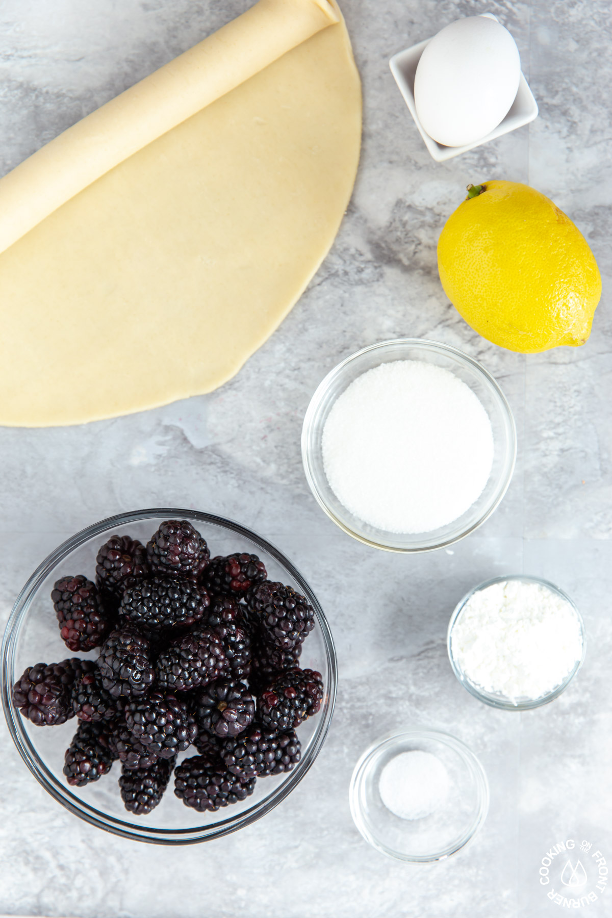 unbaked pie crust, sugar, cornstarch, salt, a lemon and fresh blackberries on a board