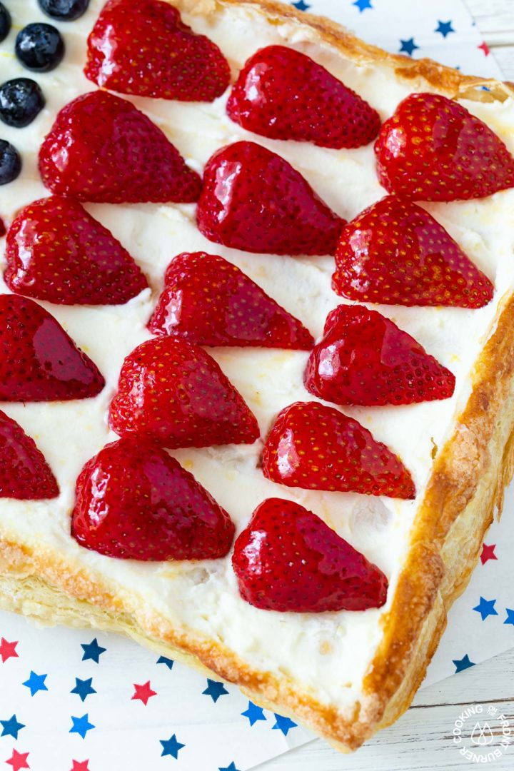 a close up picture of an american flag tart with glazed strawberries