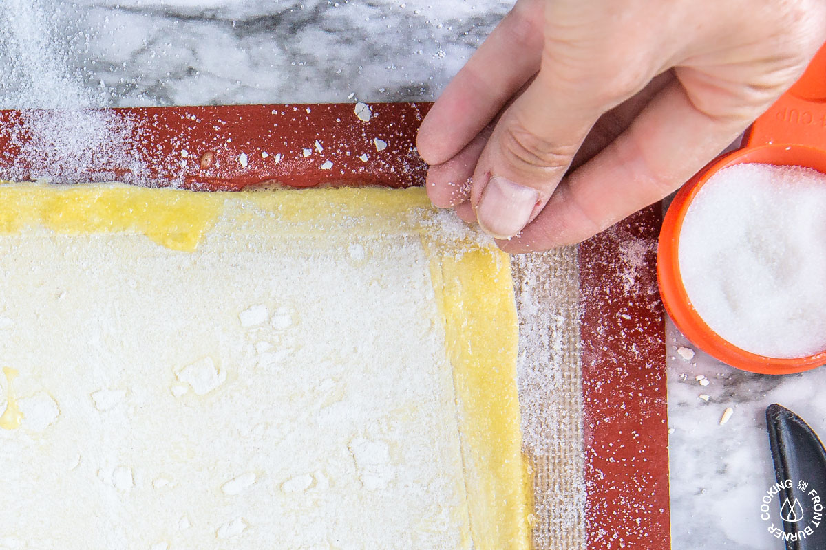 sprinkling sugar on puff pastry over an egg wash