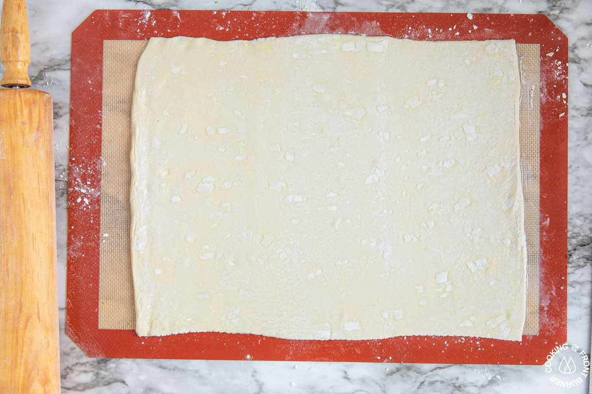 "a sheet of thawed puff pastry on a silpat mat rolled in a 10x12"" shape"