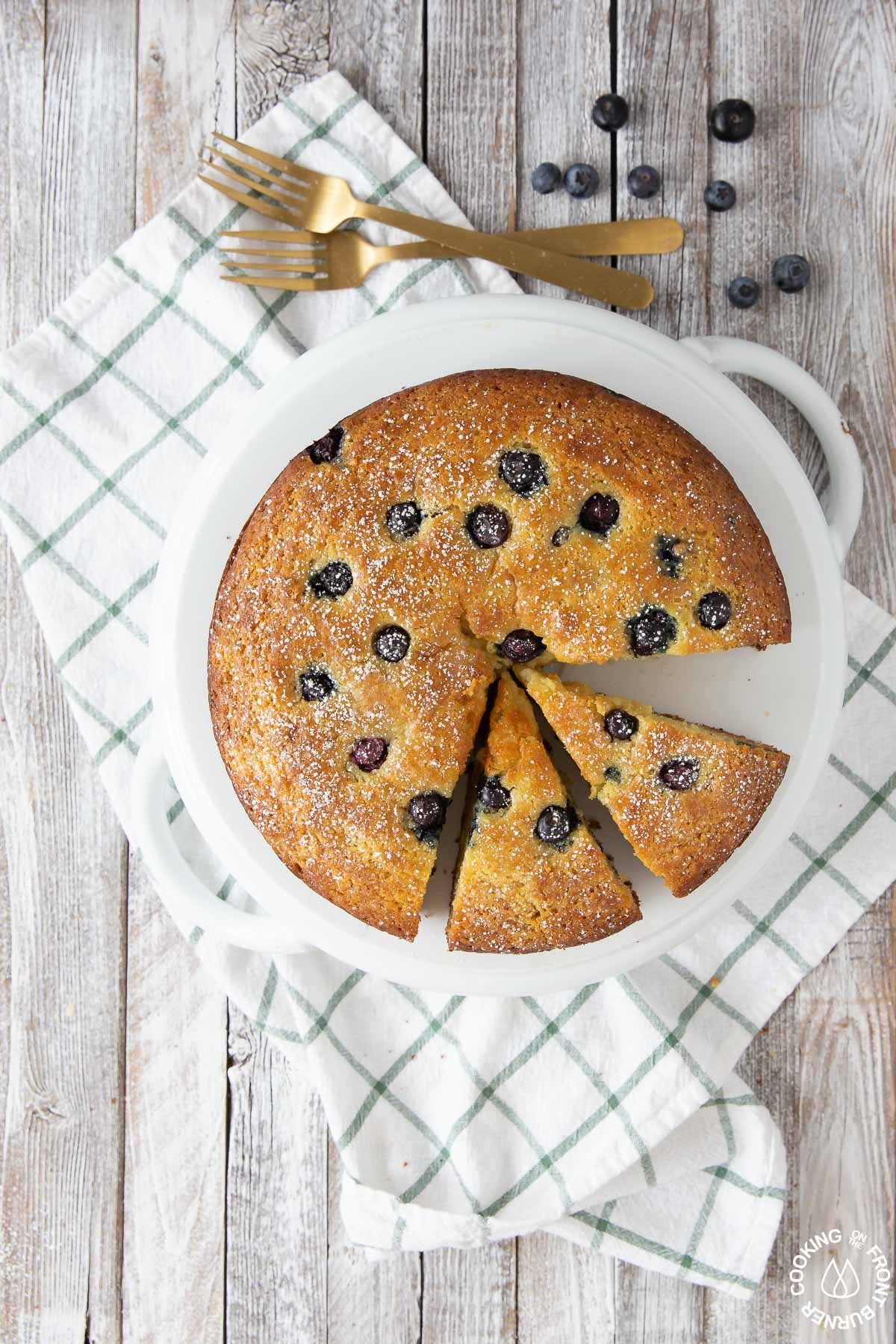 a lemon blueberry ricotta cake on a plate with two slices cut into it