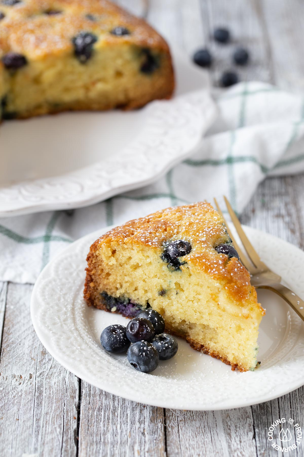 a slice of lemon blueberry ricotta cake on a plate with a fork next to it
