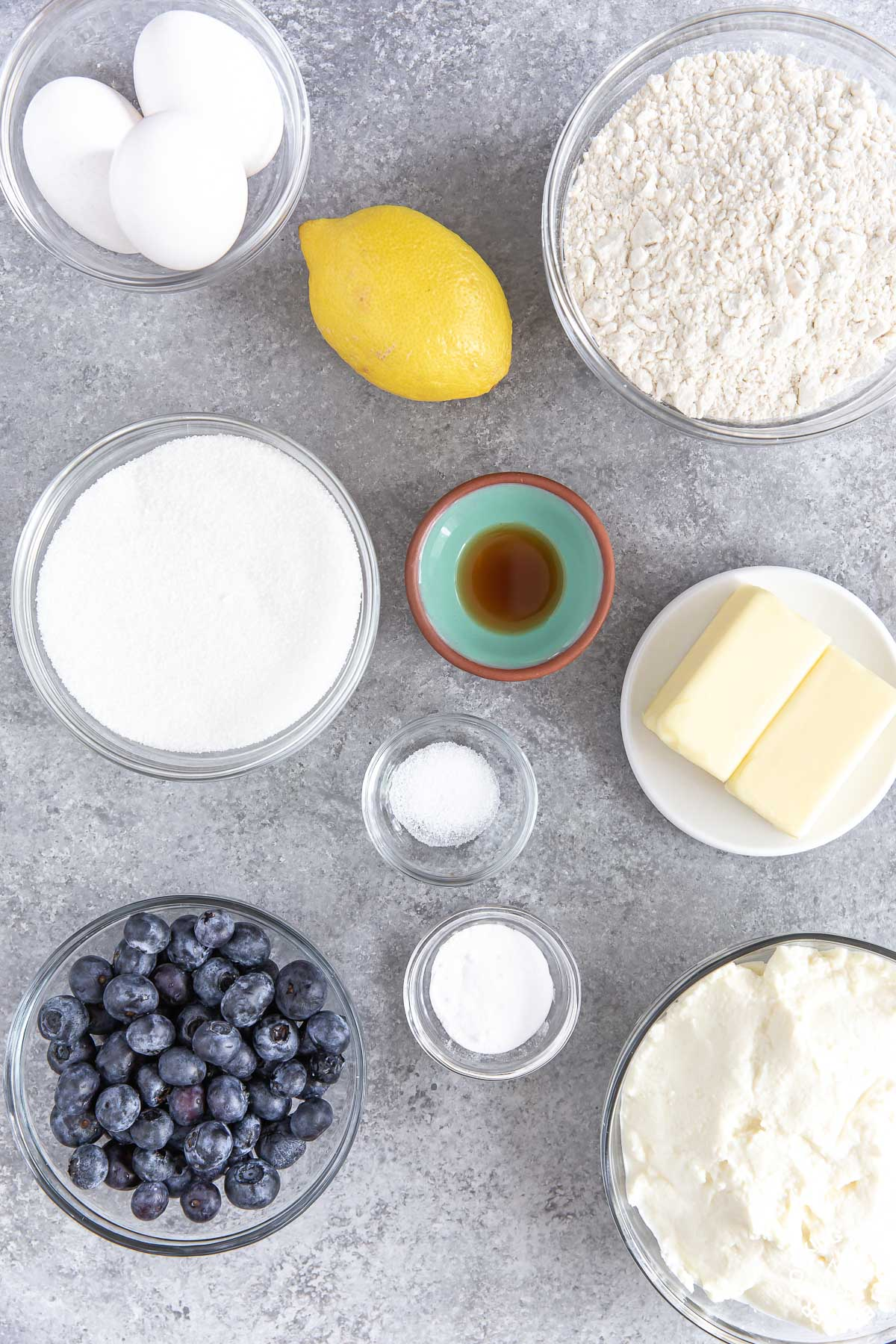 flour, sugar, lemon, vanilla extract, eggs, blueberries ricotta cheese and butter in bowls on a counter