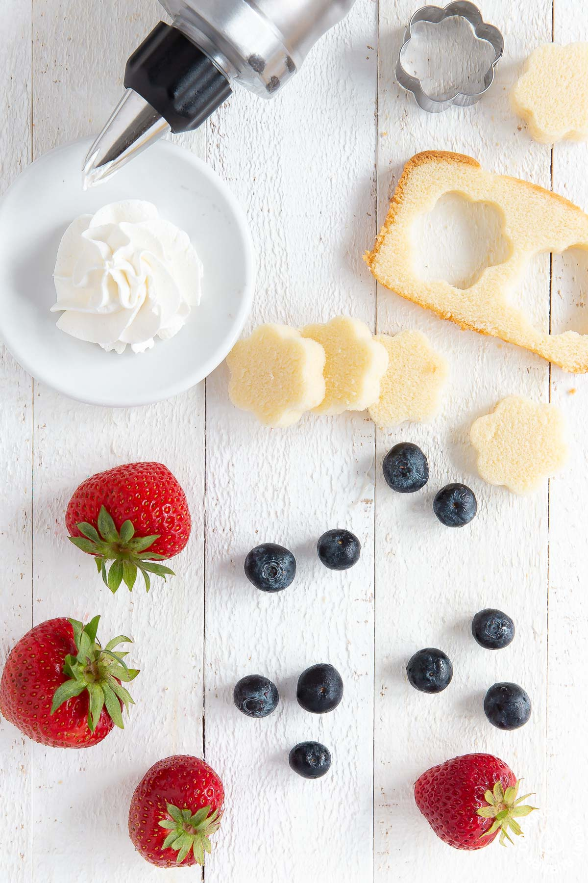 pound cake, cool whip, fresh strawberries and blueberries on a cutting board - overhead view