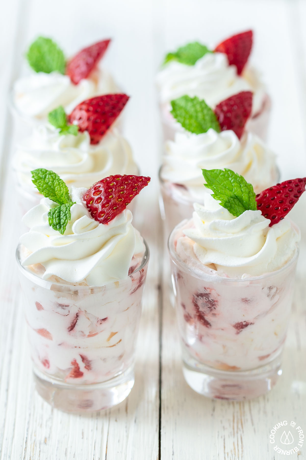 6 small shot glasses filled with strawberry filling and topped with cool whip and a mint leaf