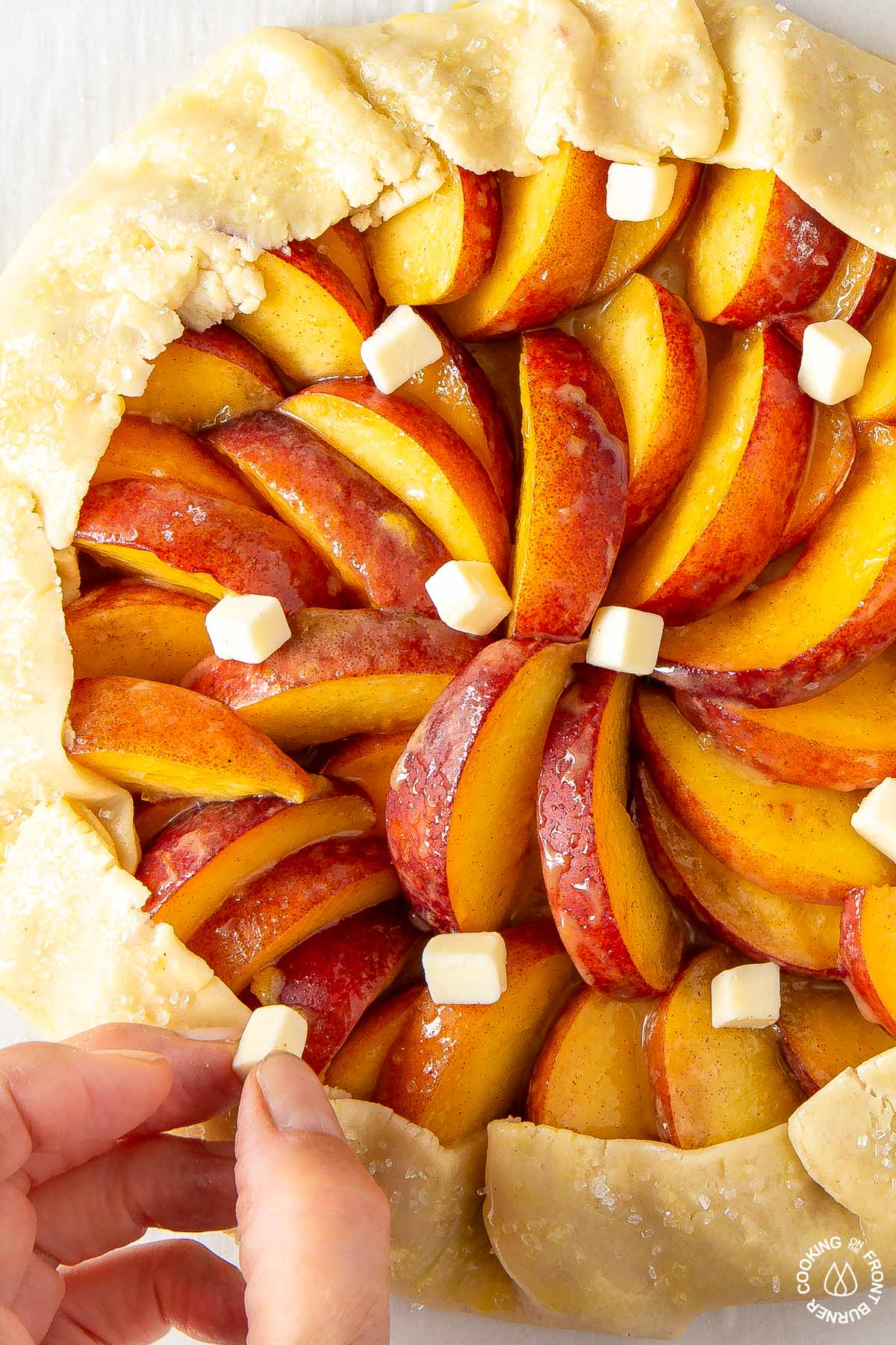 placing small pieces of butter on a unbaked peach galette