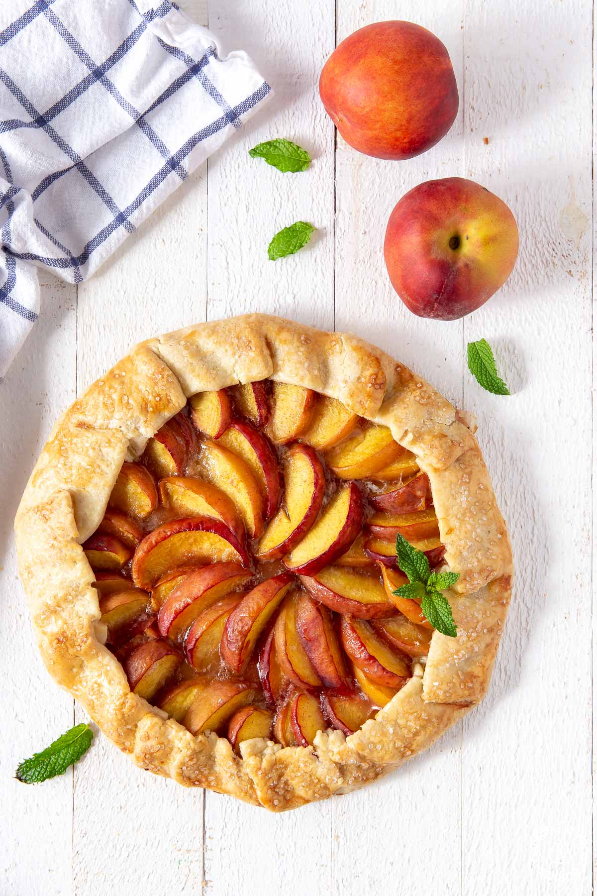 a peach galette on a board unsliced
