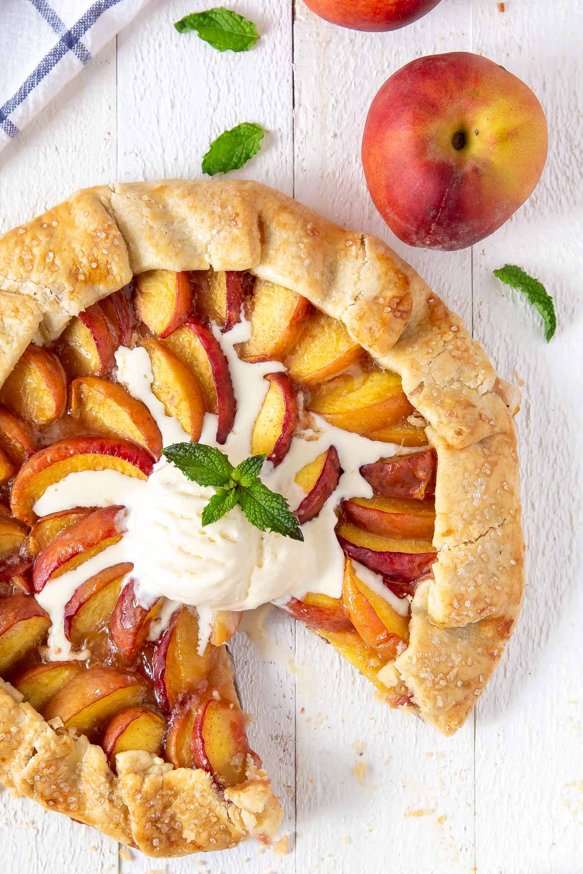 peach galette topped with vanilla ice cream with a slice cut out