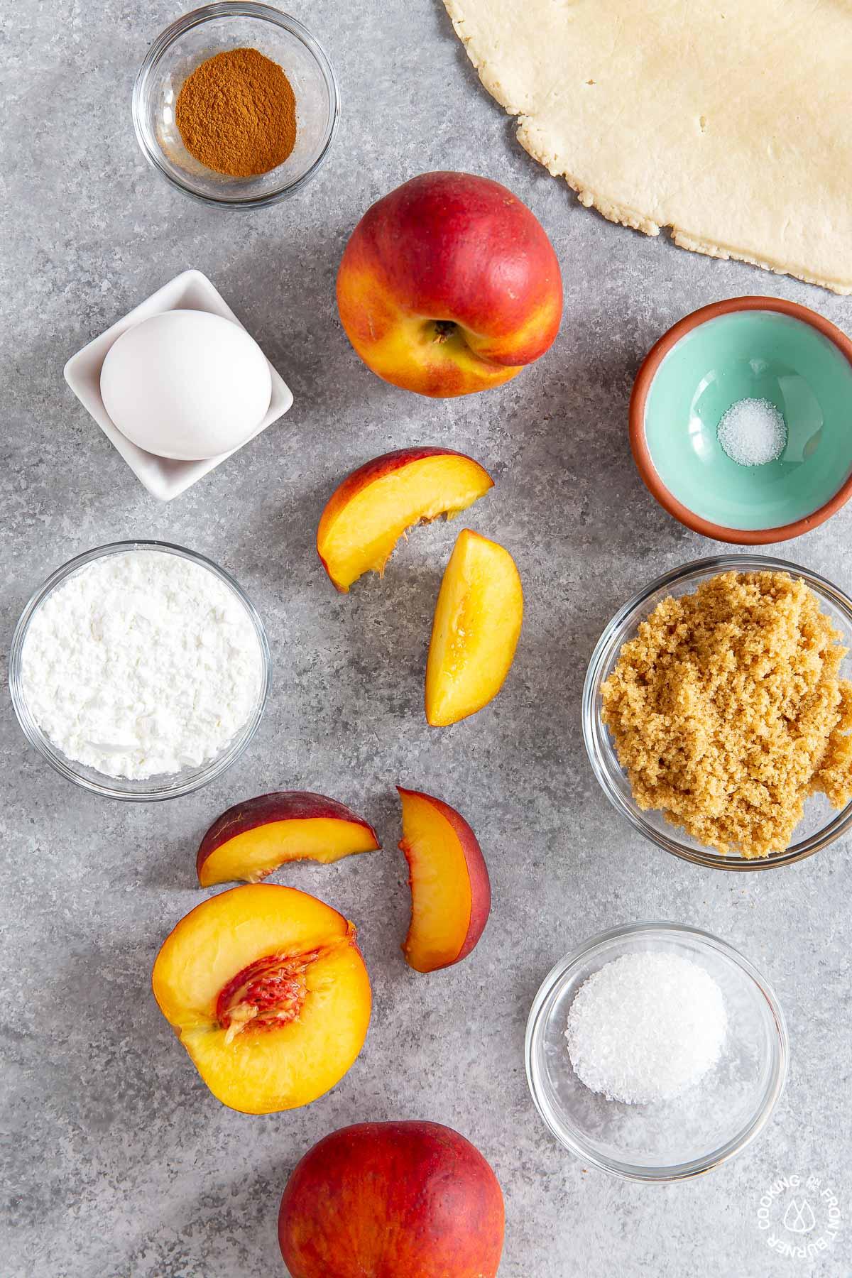 fresh peaches, grown sugar, cinnamon, egg, salt, cornstarch in bowls on a board