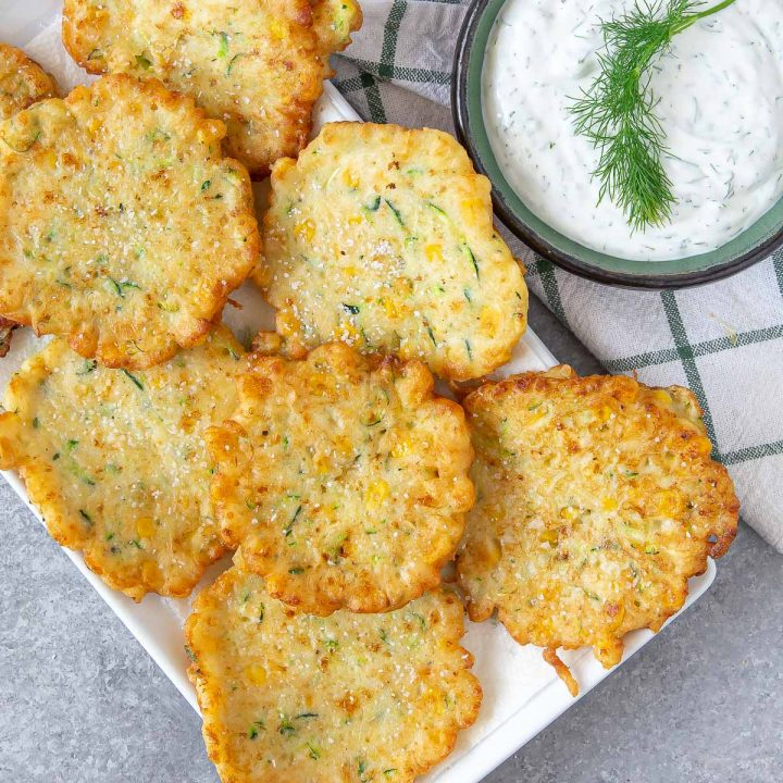 a plate with friend corn zucchini fritters and a side of dill dip