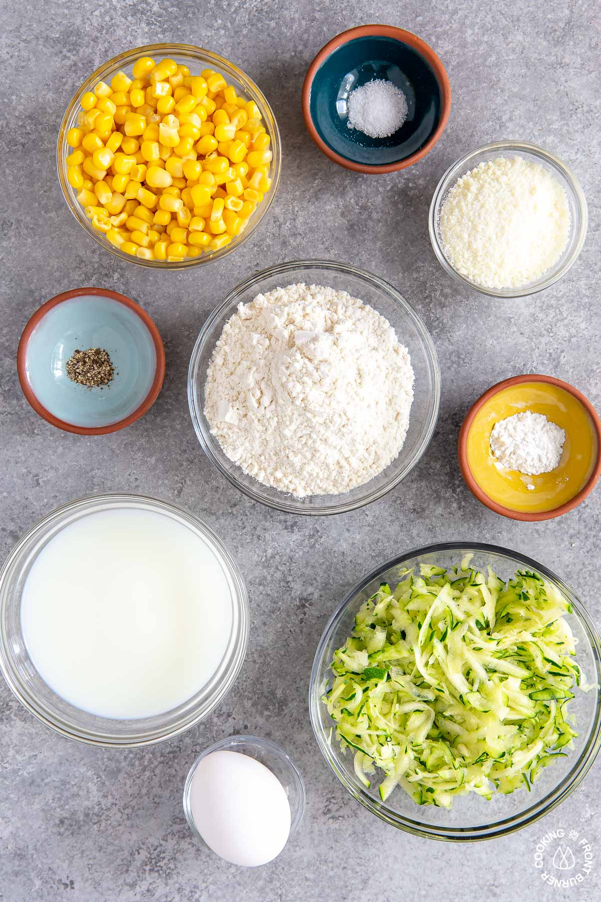 in bowls-corn, grated zucchini, cheese, salt, pepper, milk, flour, baking powder