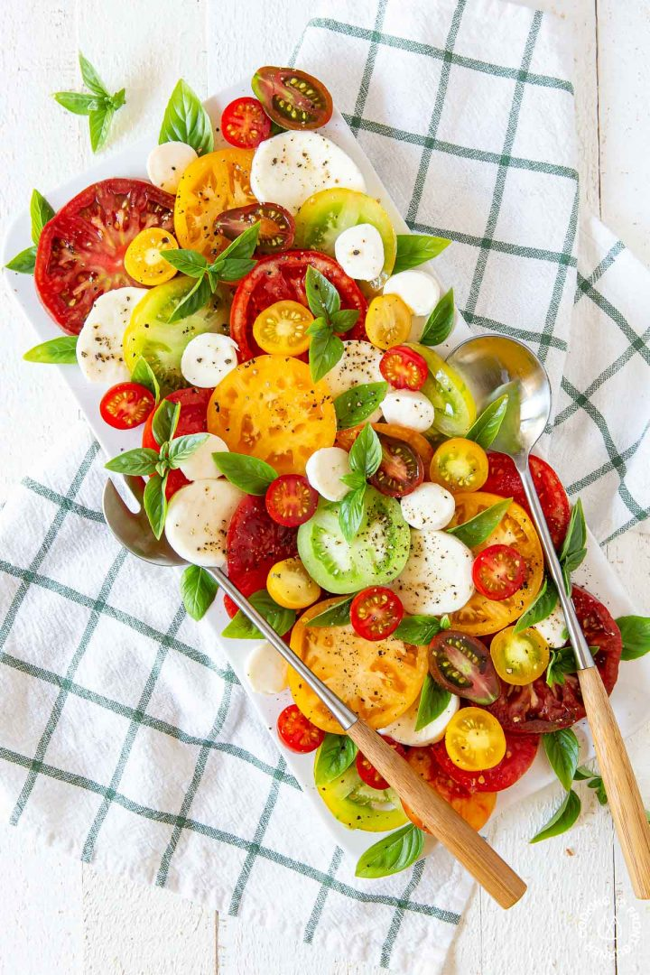 caprese salad on a white platter with a big fork and spoon