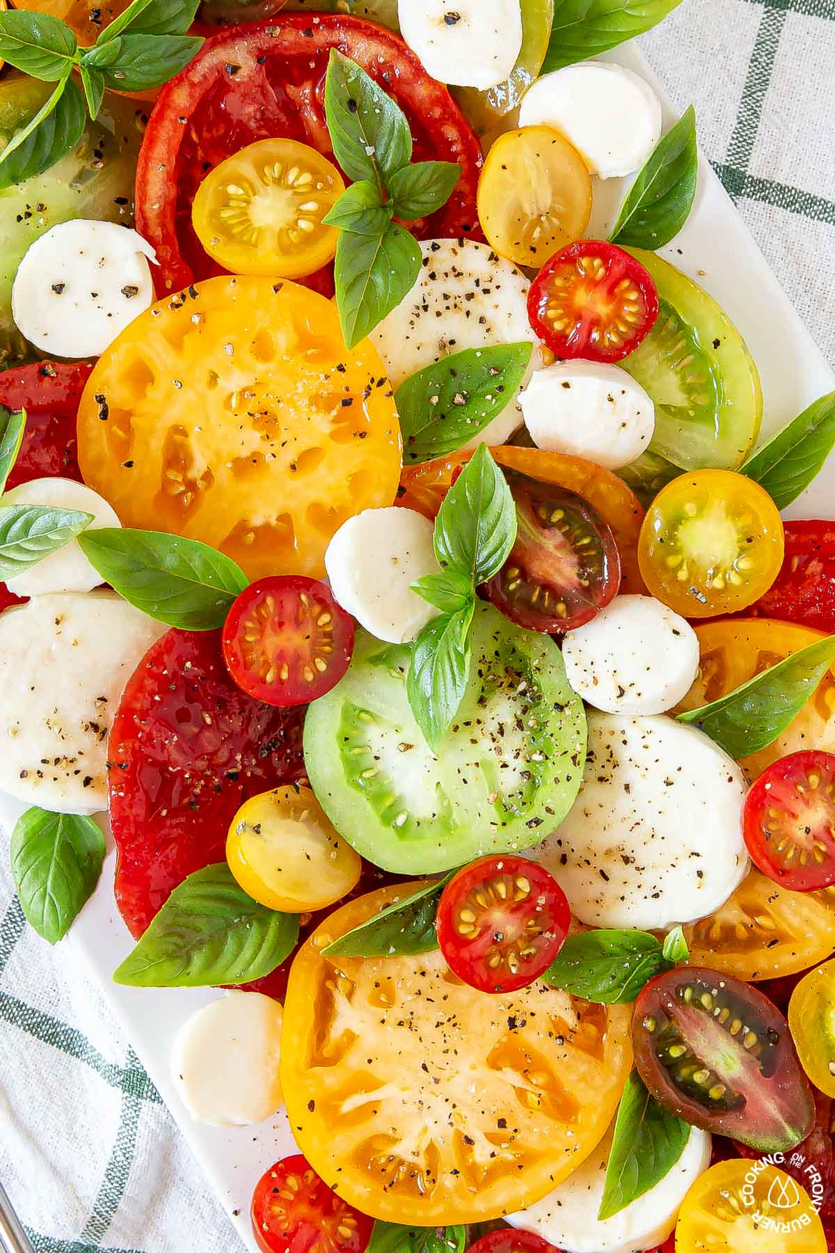a close up shot tomatoes, basil, cheese - caprese salad on a white platter