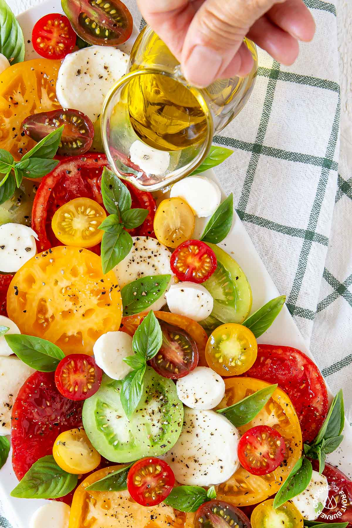 drizzling olive oil over a caprese salad on a white platter
