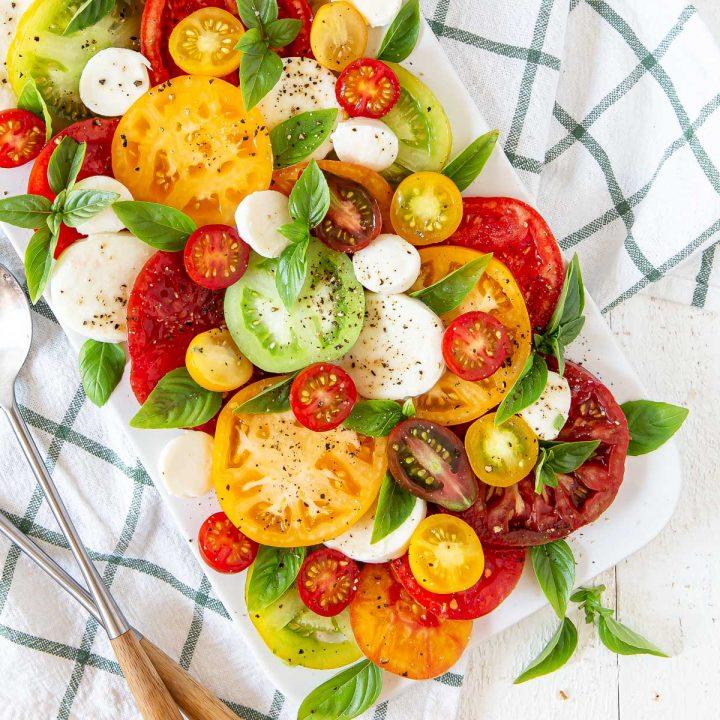 tomatoes, mozzarella, basil on a white plate