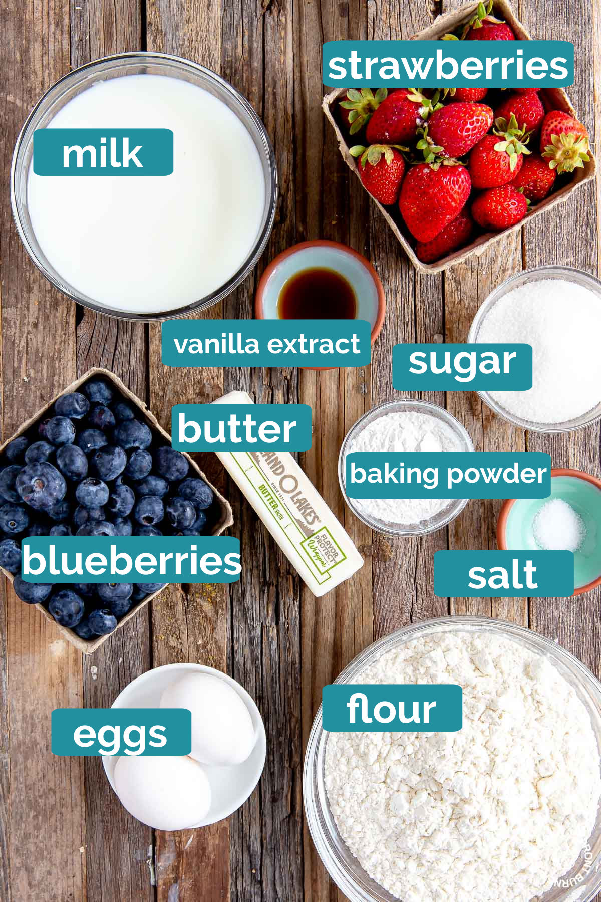 milk, strawberries, vanilla extract, blueberries, sugar, baking powder, salt, eggs and flour on a board in bowls