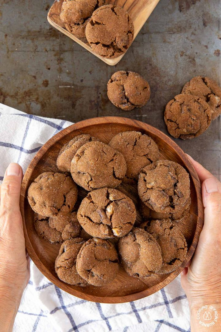 a plate of triple ginger chocolate cookies being held by 2 hands
