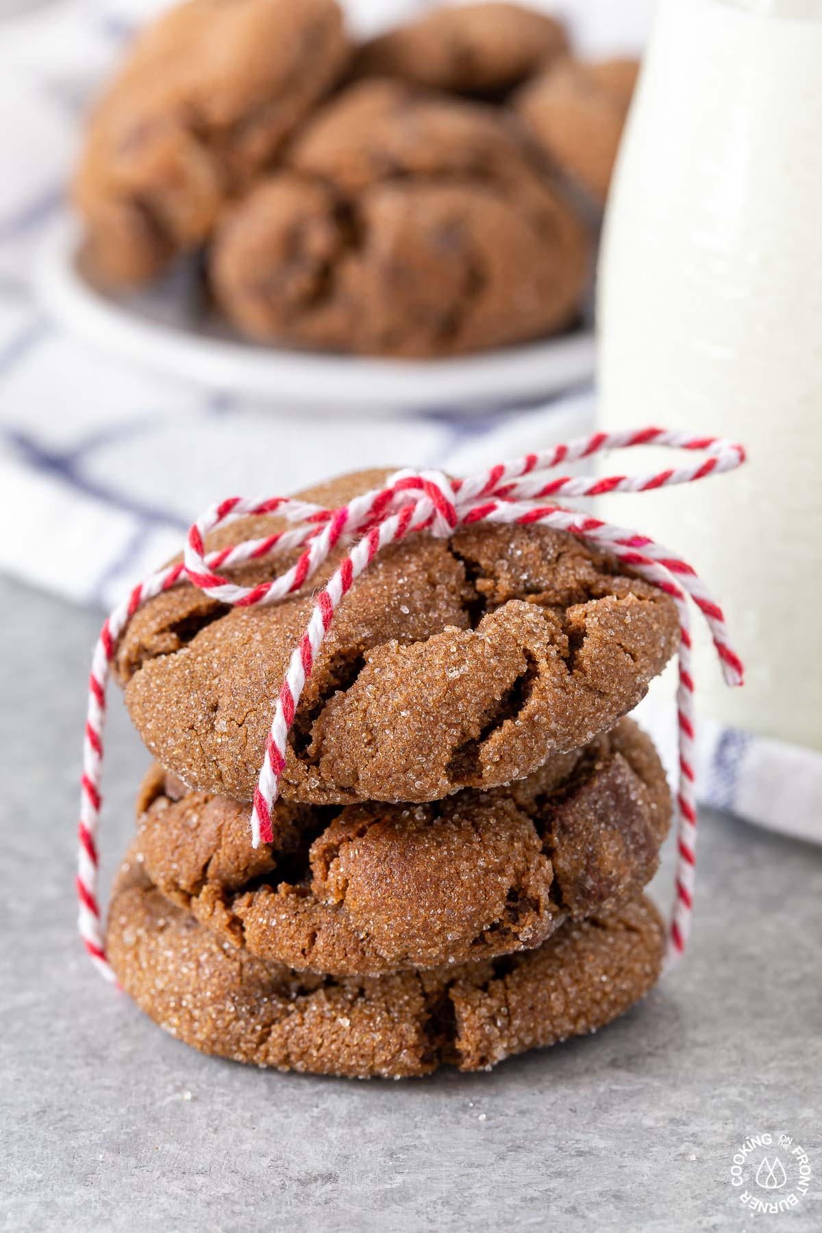 2 triple ginger cookies tied with a string by a small bottle of milk