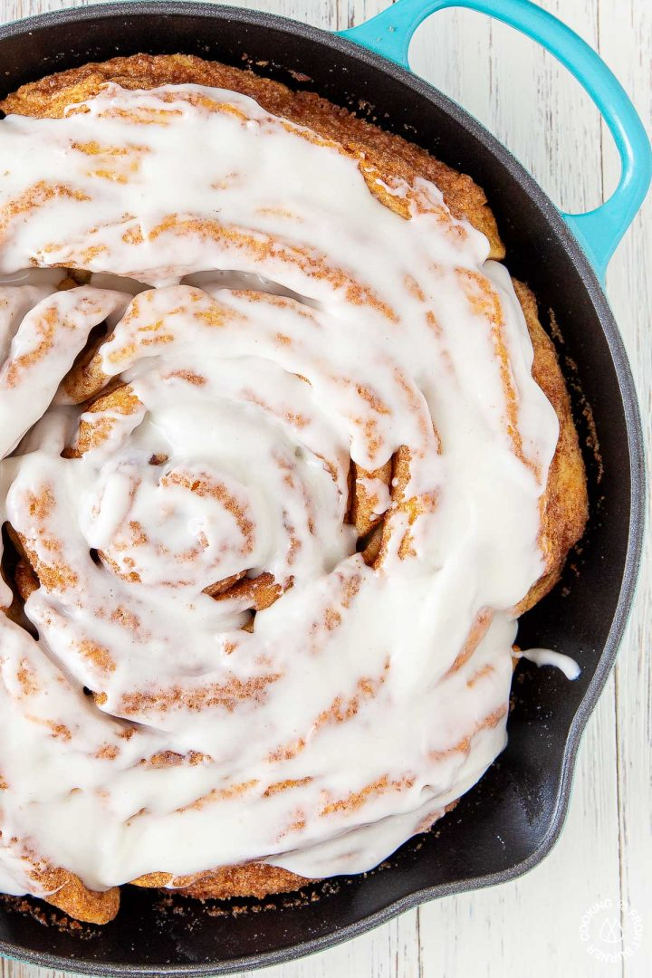 giant cinnamon roll in a turqouise skillet