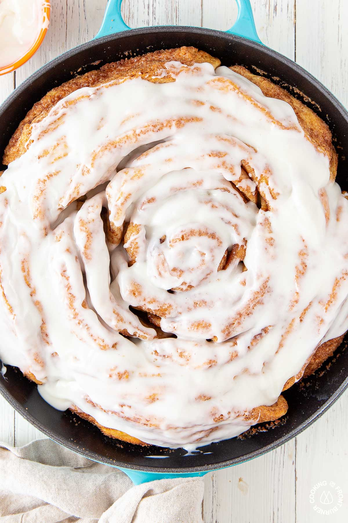 a close up picture giant cinnamon roll in a skillet