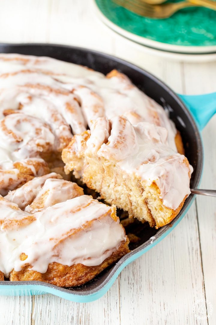 a slice of a skillet cinnamon roll on a spatula coming out of a skillet
