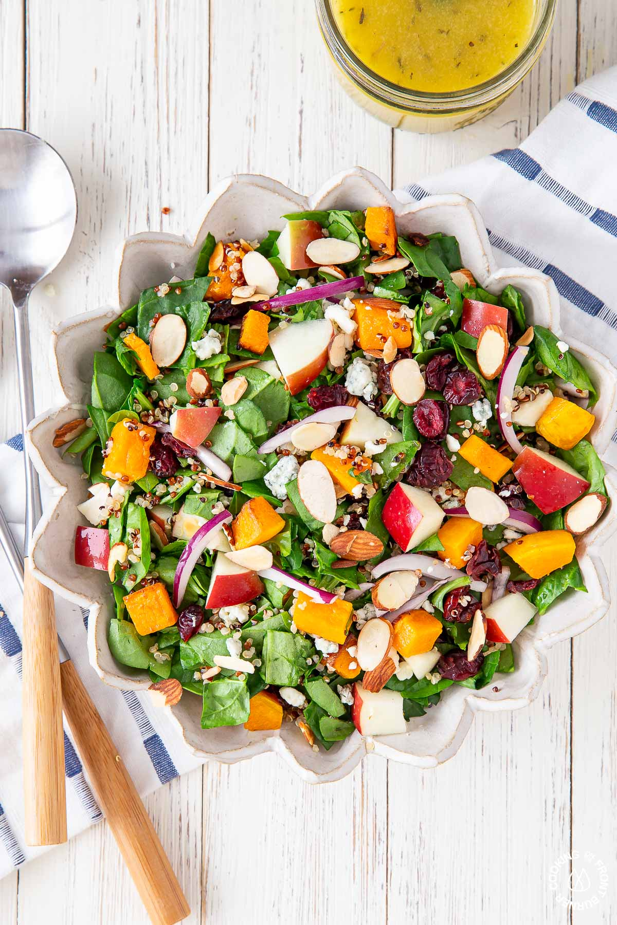 chopped spinach fall salad in a white bowl