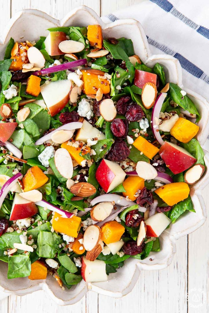 chopped spinach, almonds, blue cheese, butternut squash, apples, red onions in a bowl